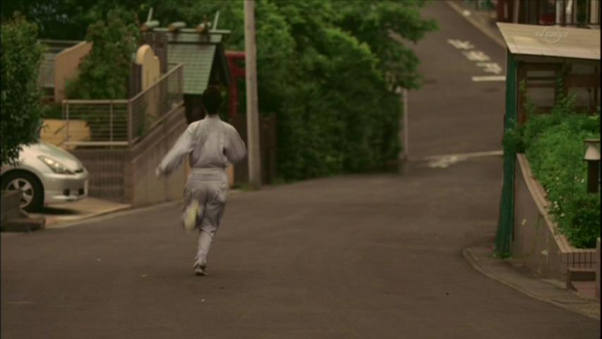 坂道を走り降りる黒木華。左にあるシルバーの乗用車と、電信柱の横にある鳥居... 坂道を走り降りる
